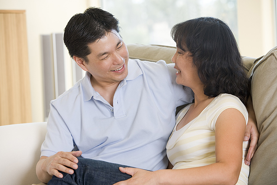 Couple relaxing in living room talking and smiling